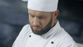 Chef-kokmens die bij professionele keuken werken Sluit omhoog het kokende voedsel van het chef-kokgezicht stock footage