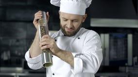 Chef-kokmens het koken bij keukenrestaurant Mannelijk chef-kok peppering voedsel bij keuken stock footage