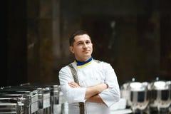Chef-kokportret in wit bij het restaurantbuffet met hete schotels stock afbeelding