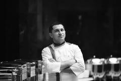 Chef-kokportret in wit bij het restaurantbuffet met hete schotels zwart-witte tonen royalty-vrije stock fotografie