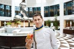 Chef-kokportret in wit bij het restaurantbuffet met rood met gele appel, gastronomisch, voedingsconcept royalty-vrije stock afbeeldingen