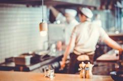 Chef-koks die in de keuken koken Stock Afbeeldingen