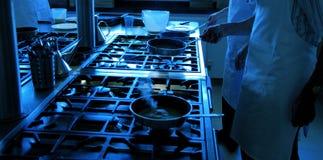Chef-koks die met pannen werken stock foto