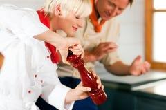 Chef-koks in restaurant of hotelkeuken het koken Stock Afbeeldingen