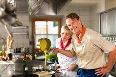 Chef-koks in restaurant of hotelkeuken het koken Stock Afbeelding