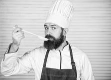 Chef-koksmaak souce van houten lepel Culinaire keuken vitamine Het gezonde voedsel koken Rijpe hipster met baard gelukkig stock afbeelding