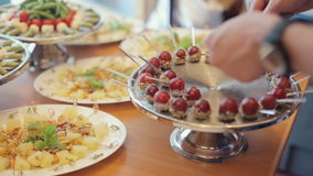 Chef lays ripe grapes in the nuts and chocolate on a large silver tray. Chef lays ripe grapes in the nuts and chocolate on large silver tray stock footage