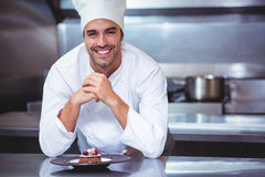 Chef leaning on the counter with a dessert Stock Photo