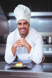 Chef leaning on the counter with a dish Royalty Free Stock Image