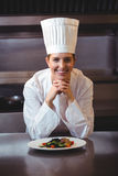 Chef leaning on the counter with a dish. In the kitchen Royalty Free Stock Photography