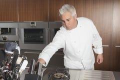 Chef Leaning For Knife in der Handelsküche Lizenzfreies Stockfoto