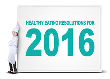 Chef leans on billboard of healthy eating resolutions. Confident female chef leans on a big board with a text of healthy eating resolutions for 2016 Stock Photo