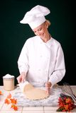 Chef lifting dough. Passive posed uniformed female Chef using a scraper to lift the pie dough up off a cold marble board Royalty Free Stock Photo