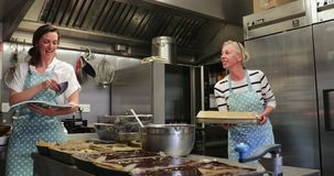 Two Chefs Preparing Desserts. A chef lifting out fresh cakes from the oven while the other chef reads a cookery book in the kitchen stock footage