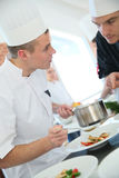 Chef listening to young cooking apprentice Royalty Free Stock Images
