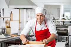 Chef Looking Away While Rolling Pasta Sheet At Stock Images