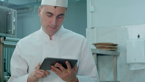 Chef looking for recipes on digital tablet in the professional kitchen stock footage