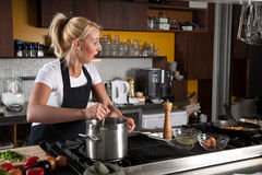 Chef looking shocked. Female chef looking shocked while stirring in the pan Stock Image