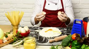 Chef makes dough. Male hands hold broken egg shells. On white brick wall background. Cook in burgundy uniform works by table with vegetables and kitchenware Stock Photos