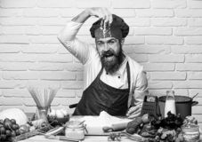 Chef makes dough. Professional cookery concept. Man with beard plays with flour on white brick background. Cook with. Cheerful face in burgundy uniform sits by royalty free stock images