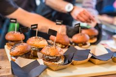Chef making beef burgers outdoor on open kitchen international food festival event. Street food ready to serve on a food stall Stock Photography