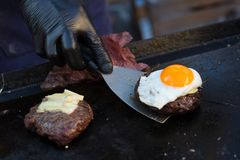 Chef making beef burgers outdoor on open kitchen international food festival event. Royalty Free Stock Images