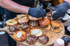 Chef making beef burgers outdoor on open kitchen international food festival event. Stock Images