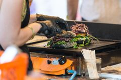 Chef making beef burgers outdoor on open kitchen international food festival event. Royalty Free Stock Photography