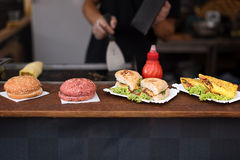 Chef making beef burgers outdoor on open kitchen international street food festival event. Royalty Free Stock Photo