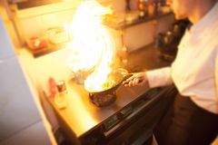 Chef is making flambe. With pan and fire stock photo