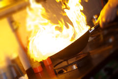 Chef is making flambe. With pan and fire Royalty Free Stock Photography