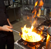 Chef is making flambe dish. On restaurant kitchen Stock Photography