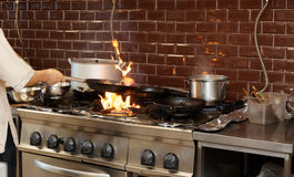 Chef is making flambe dish. In restaurant kitchen Royalty Free Stock Photography