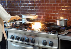 Chef is making flambe dish in restaurant kitchen Stock Image