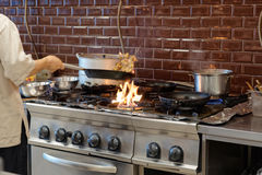 Chef is making flambe dish in restaurant kitchen Royalty Free Stock Photos