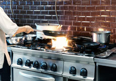 Chef is making flambe dish in restaurant kitchen, toned Royalty Free Stock Images