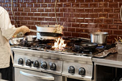 Chef is making flambe dish in restaurant kitchen, toned Stock Photography