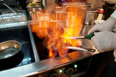 Chef is making flambe with cognac. Chef is making flambe igniting cognac with gas torch Royalty Free Stock Photo