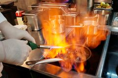 Chef is making flambe with cognac. Chef is making flambe igniting cognac with gas torch Stock Image