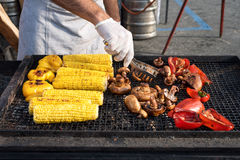 Chef making grilled vegetables outdoor on open kitchen international street food festival event. Stock Photo