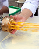 Chef making pasta with machine Stock Images