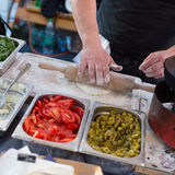 Chef making pita bread for falafel roll outdoor on street stall. Stock Photos