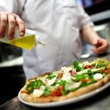 Chef making pizza at kitchen Stock Photo