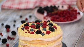 Chef making puff pastry cake with custard and currant berries, raspberries, blackberries, blueberries. Delicious dessert.  stock footage