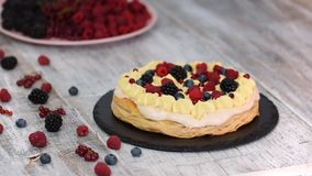 Chef making puff pastry cake with custard and currant berries, raspberries, blackberries, blueberries. Delicious dessert.  stock video