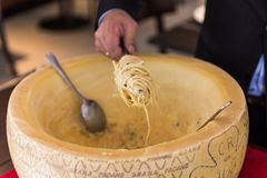 Chef making spaghetti carbonara in cheese wheel with tourched brandy and fried bacon.  Stock Photography
