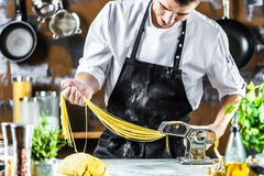 Chef making spaghetti noodles with pasta machine on kitchen table with some ingredients around royalty free stock image