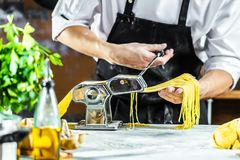 Chef making spaghetti noodles with pasta machine on kitchen table with some ingredients around royalty free stock images