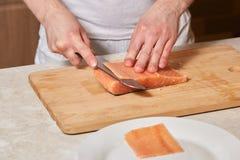 Chef making sushi rolls. Cutting salmon fish on wooden board. Chef making sushi rolls. Hands cutting salmon fish on wooden board Royalty Free Stock Photography