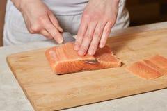 Chef making sushi rolls. Cutting salmon fish on wooden board. Chef making sushi rolls. Hands cutting salmon fish on wooden board Stock Photography
